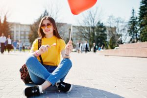Healthy Young Adult Happy Eating a Lollipop